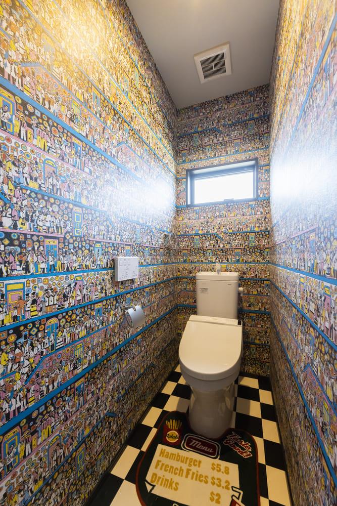 「ウォーリーを探せ」のアクセントクロスと市松模様のクッションフロアを採用した遊び心のあるトイレ