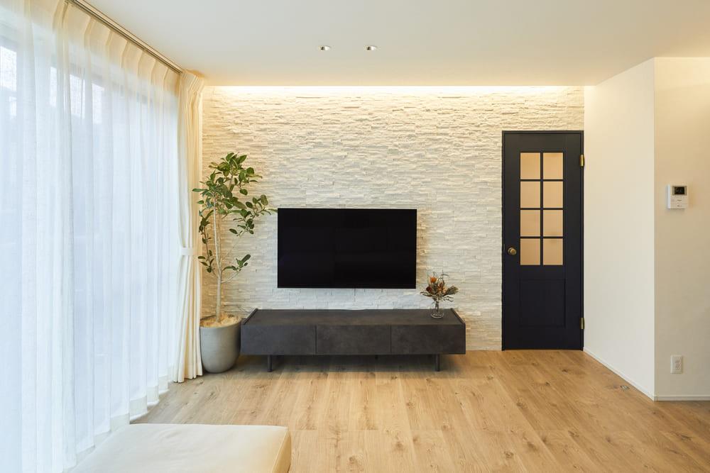 TV後ろの壁には、ホワイトの一面タイルを施工し、上部に間接照明を取り付けることでタイルの凹凸感が際立っている。また、壁掛けTVにしたことでスッキリとした空間になった