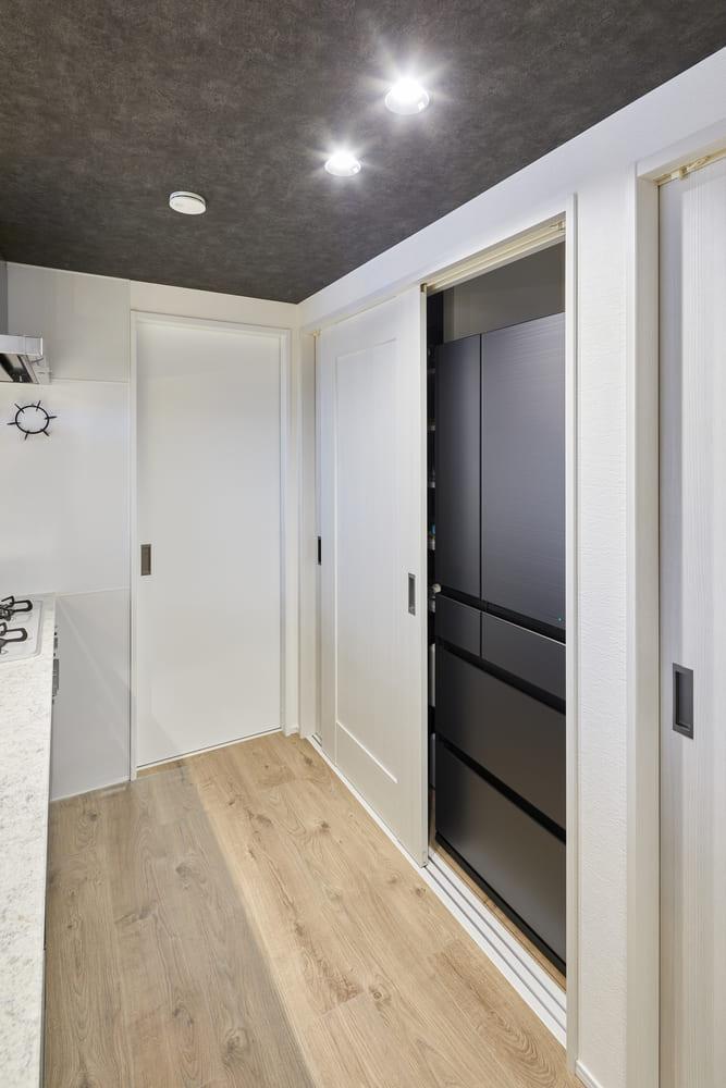 収納力豊富なパントリーは敷居を設けた。来客の際には扉をしめることで生活感を隠すことができる