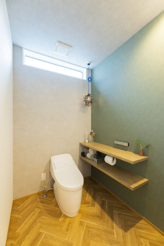 オープンな収納棚を取り付けた広々としたトイレ。床はヘリンボーン張りに仕上げ、かわらしいデザインとなった