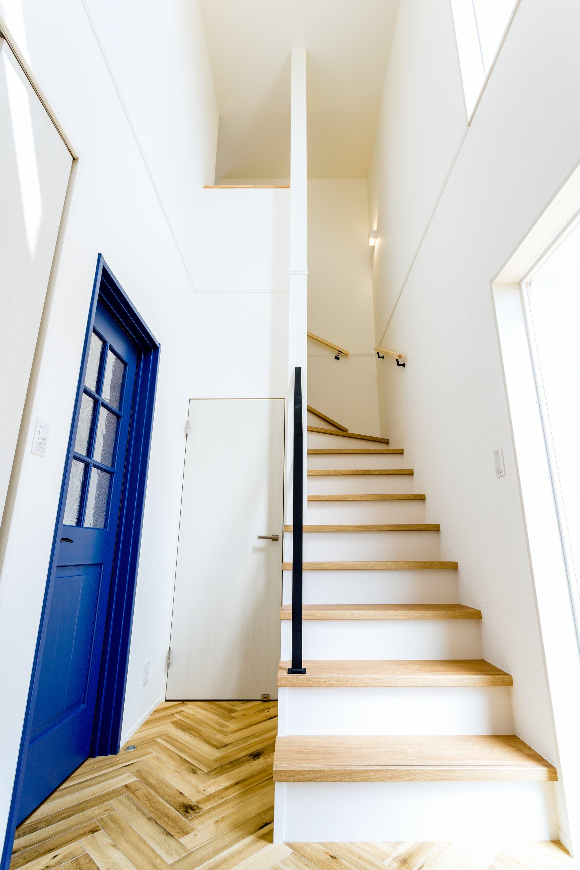 ヘリンボーン貼りの床とブルーのリビングドアが印象的な玄関ホール