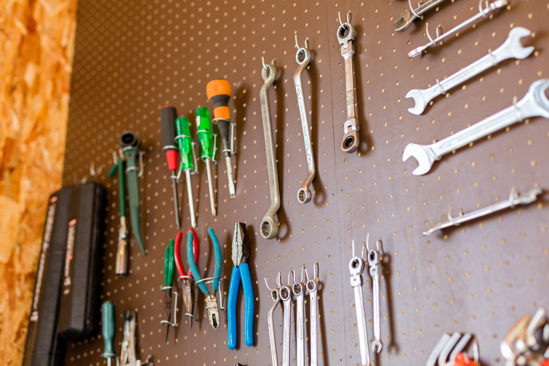 ガレージの壁は有孔ボードにフックを取り付け、 おしゃれに工具を収納